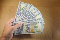 Hand holding one hundred dollar bills on wooden background