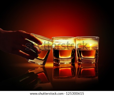Hand holding one of three glasses of whiskey with sea illustration in