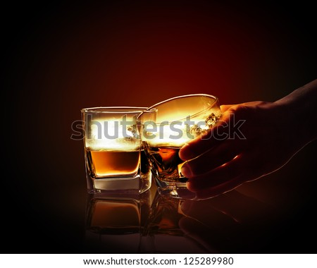 Hand holding one of two glasses of whiskey with nature illustration in #125289980