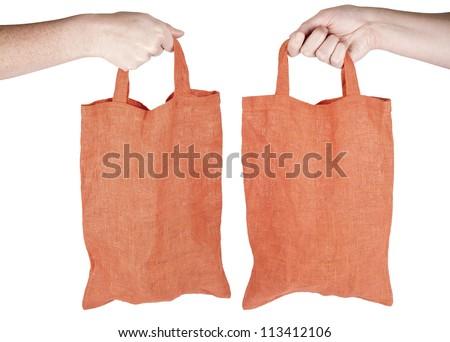 Hand holding orange fabric reusable shopping bag isolated on white