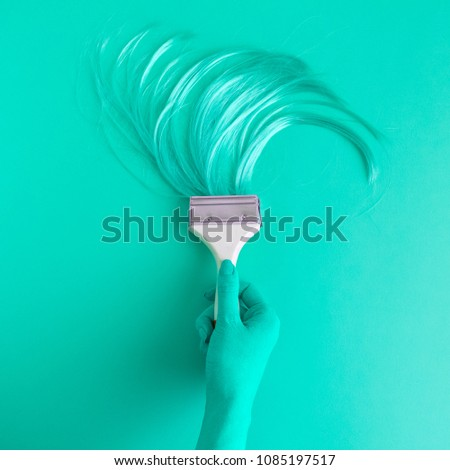 Hand holding paintbrush with long hair minimal abstract turquoise creative concept.