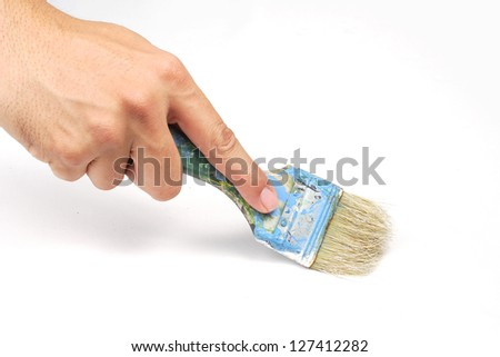 Hand holding painting brush on white canvas