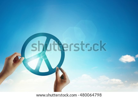 Hand holding paper cut of peace sign at blur sky and lens flare. freedom and peace concept. #480064798