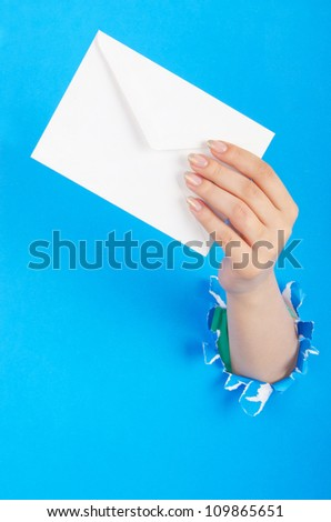 Hand holding paper envelope from hole