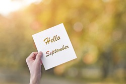 Hand holding paper with Hello September text over blur nature background. Autumn concept.