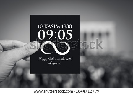 Hand holding paper with hour of the death and date of Ataturk in front of blurry Anitkabir mausoleum in November 10.  English of message: We remember you with respect, longing and gratitude. Foto d'archivio ©