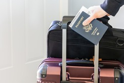 Hand holding passport and approved vaccination card with laptop bag and luggage ready for business trip. Vaccine document and citizen identity of passenger, traveler require for travel in new normal.