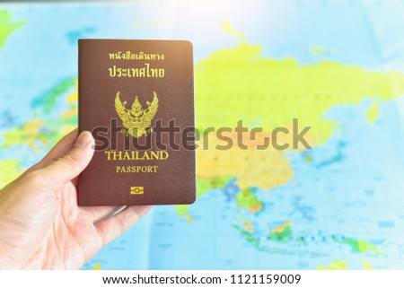 Hand Holding Passport Book with World Map Background #1121159009