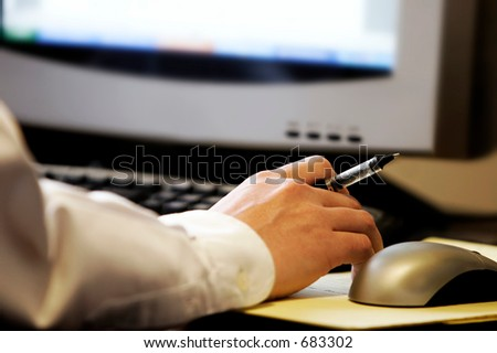 Hand holding pen in front of  computer screen, with mouse and keyboard - represents computer work and research.