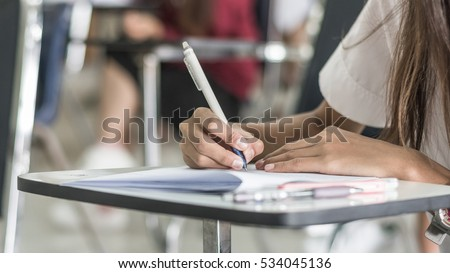 Hand holding pen writing doing education examination in university classroom: School students having exam testing ELO expected learning outcome: Young asian adult college people study in class room