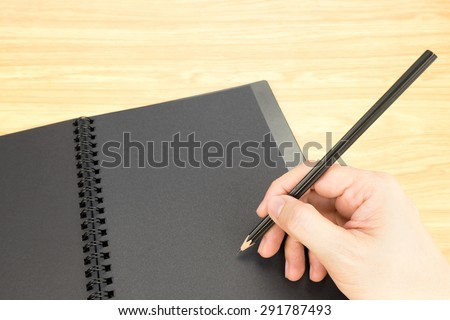 hand holding pencil writing on blank black book with table and business card on wooden table, Mock up for adding your content.