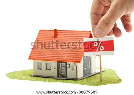 Hand holding percent-sign in front of model house - real estate discount concept
