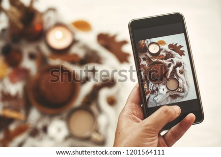 Hand holding phone and taking photo of stylish autumn flat lay of coffee,cookies, fall leaves, candle, berries, nuts, acorns,cotton on soft white background. Modern food photography