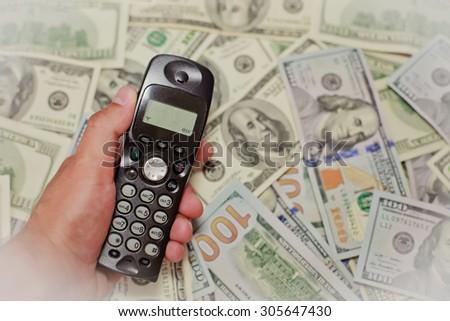 Hand holding phone on Money, online banking make money concept.