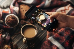 hand holding phone taking photo of stylish winter flat lay coffee cookies and spices on wooden rustic background. cozy mood autumn. instagram blogging workshop concept.