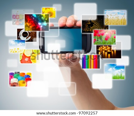 Hand holding phone with multimedia - stock photo