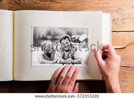Hand holding photo album with pictures of senior couple. Studio #572355220