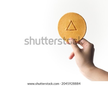 hand holding piece of Dalgona honeycomb toffee sugar candy with triangle shape stamp on white background