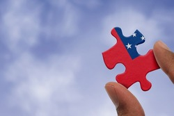 Hand holding piece of jigsaw puzzle with flag of Samoa. Jigsaw puzzle of Samoa flag on sky background.