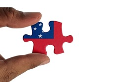 Hand holding piece of jigsaw puzzle with flag of Samoa. Jigsaw puzzle of Samoa flag on white background.