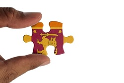 Hand holding piece of jigsaw puzzle with flag of Sri Lanka. Jigsaw puzzle of Sri Lanka flag on white background.