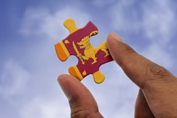 Hand holding piece of jigsaw puzzle with flag of Sri Lanka. Jigsaw puzzle of Sri Lanka flag on sky background.