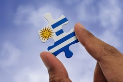 Hand holding piece of jigsaw puzzle with flag of Uruguay. Jigsaw puzzle of Uruguay flag on sky background.