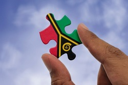 Hand holding piece of jigsaw puzzle with flag of Vanuatu. Jigsaw puzzle of Vanuatu flag on sky background.