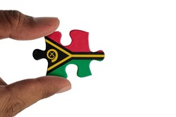 Hand holding piece of jigsaw puzzle with flag of Vanuatu. Jigsaw puzzle of Vanuatu flag on white background.