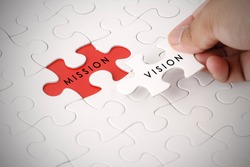 Hand holding piece of jigsaw puzzle with VISION and MISSION wording