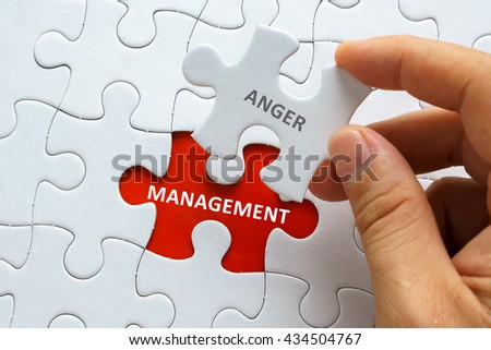 Hand holding piece of jigsaw puzzle with word ANGER MANAGEMENT. #434504767