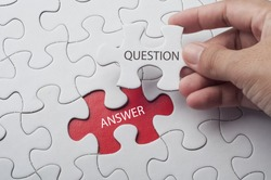 Hand holding piece of jigsaw puzzle with word question & answer.