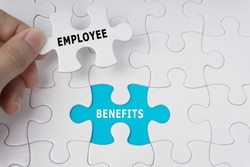 Hand holding piece of jigsaw puzzle with words Employee Benefits.