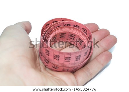 hand holding pink measuring tape, to control body measurements or use of seamstresses, isolated on white background