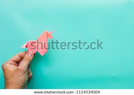 Hand holding pink trendy geometrical polygonal paper origami unicorn on blue background. Empty space. Horizontal poster, postcard, banner template.