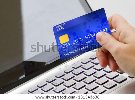 hand holding plastic card  on open notebook background