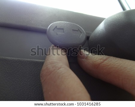 Hand Holding Plastic Hook of Coat Hanger for Hanging Cloths in A Car.