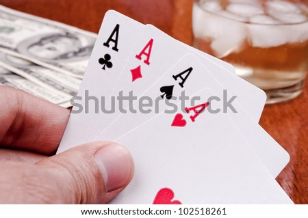 Hand holding poker of aces with dollar bills and whiskey in the background - stock photo