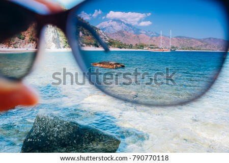 hand holding polarization sunglasses against blue sky and sea, summer vacation journey and concept, looking through glasses #790770118