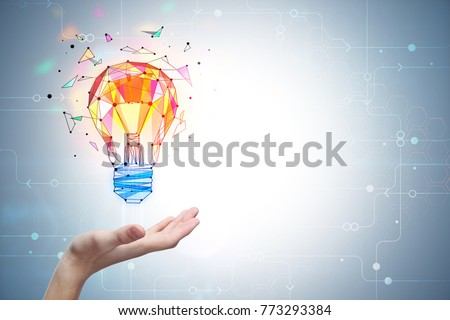 Hand holding polygonal lamp on grey background with copyspace. Enlightenment and innovation concept. 3D Rendering