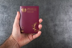 Hand holding Portuguese passport with gray background.