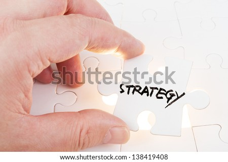Hand holding puzzle piece which written strategy word and inserting it into group of white paper jigsaw puzzles