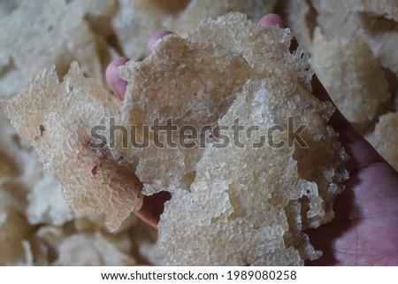Hand holding raw kerupuk gendar (puli, kerupuk beras, Lempeng Puli) with a natural background. Kerupuk gendar made of used rice (rice cracker) Zdjęcia stock ©