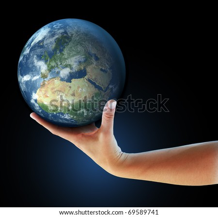 Hand holding realistic small globe symbolizing environmental care, facing Europe - stock photo