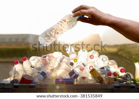 Hand holding recyclable plastic  bottle in garbage bin with sunset light #381535849