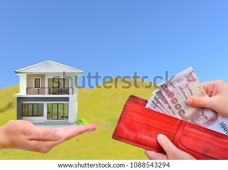 Hand holding red wallet with Thai money banknote and miniature house on a blur green field blue sky background #1088543294