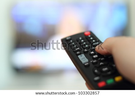 Hand holding remote control of a television