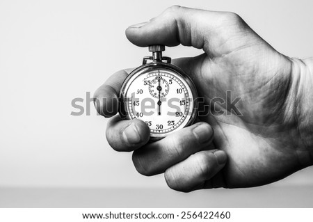 hand holding retro stopwatch in ...