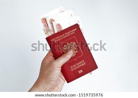 Hand holding Russian passport with 5000 rubles banknotes inside the passport on a white background, close up on the center
