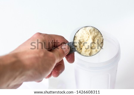Hand holding scoop of vanilla whey protein. Sports nutrition. Whey protein.